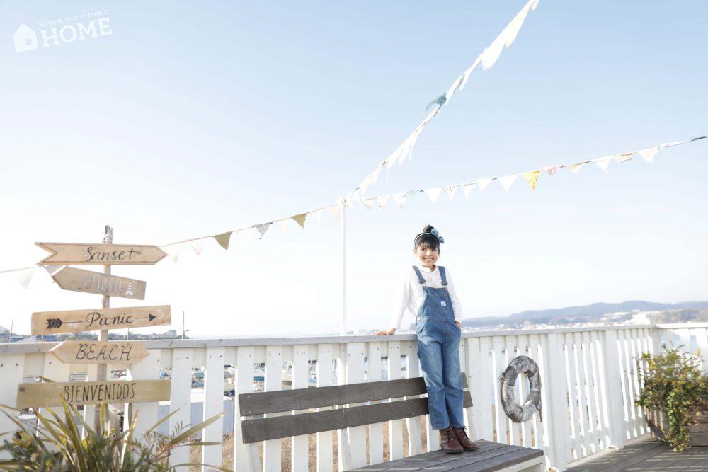 子供写真スタジオStudioHome横須賀店の海の見えるデッキで女の子が青空のしたポーズしている写真。